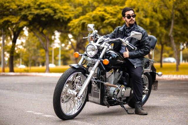 Motorkár, muž v koženej bunde sedí na motorke, namyslený.jpg