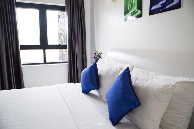 Posteľ s bielym matracom a modrými vankúšmi