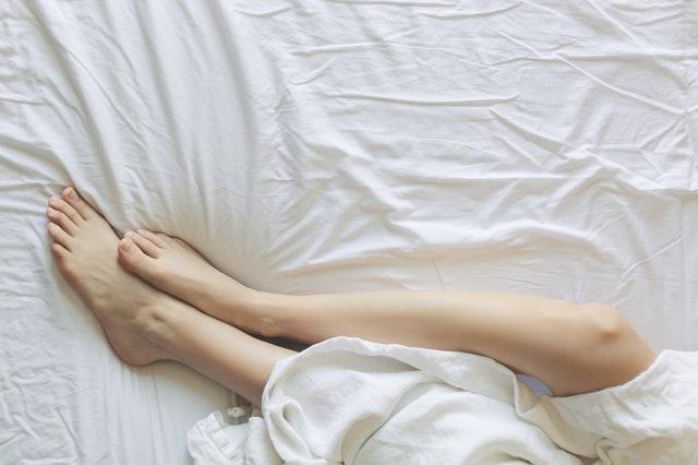 Ľudské nohy zakryté plachtou v posteli